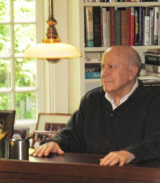 Gene Rossi sitting at a desk with window and bookcase in background