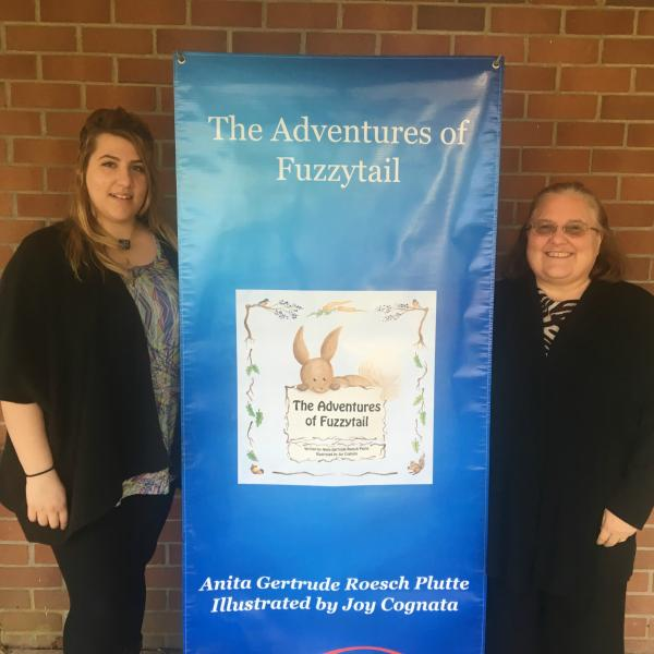 "Joy Cognata and Janet Uetz  standing on either side of a large banner reading ""The Adventures of Fuzzytail"" with book cover"