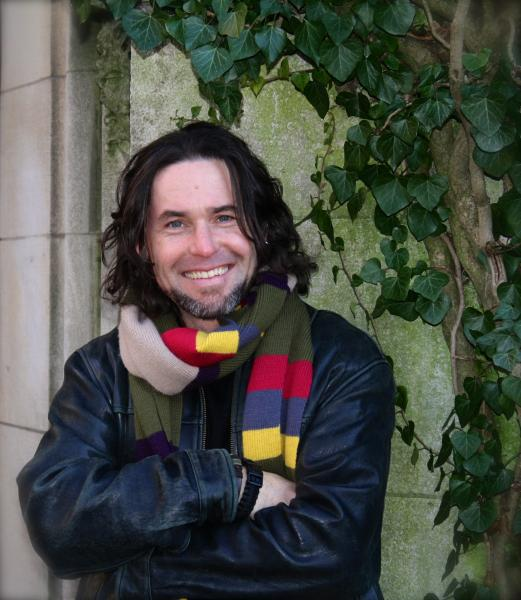 Joe McGee in black jacket and striped scarf, arms folded, smiling at camera, next to some climbing ivy.