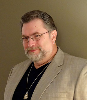 Headshot of Jonathan Maberry in tan suit, black shirt, and necklace